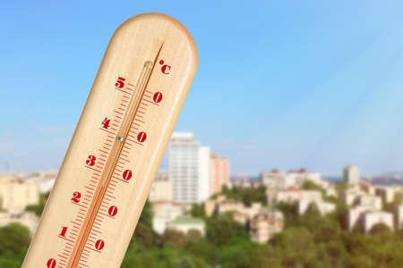 Température élevée sur le thermomètre et vue sur la ville