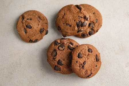 Tasty chocolate chip cookies on light background, top view