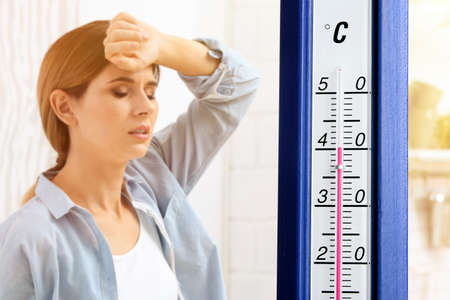 Extreme high temperature on thermometer and woman suffering from heat indoors