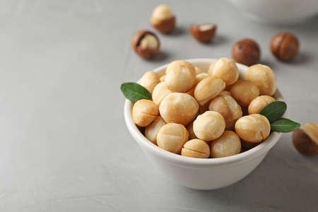 Kom met gepelde biologische Macadamia-noten en ruimte voor tekst op grijze achtergrond