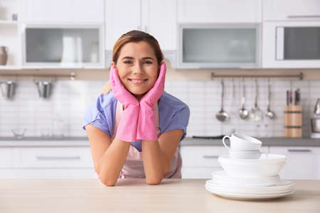 Woman in rubber gloves with clean dishes and cups in kitchen Archivio Fotografico