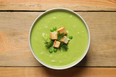 Fresh vegetable detox soup made of green peas with croutons in dish on wooden background, top view 版權商用圖片