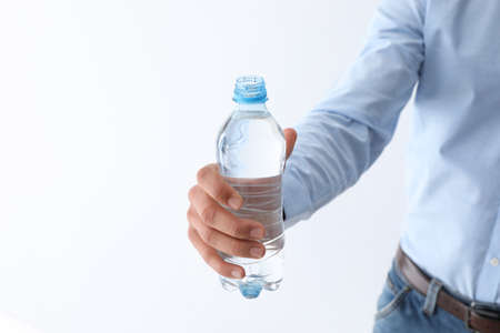 Man holding bottle of pure water on white background, closeup. Space for text Banque d'images