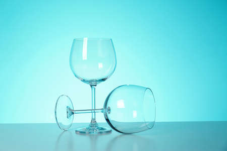 Clean wine glasses on table against color background Imagens
