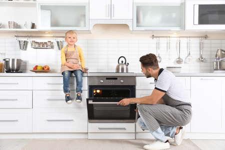 Joven y su hijo horneando algo en el horno en casa