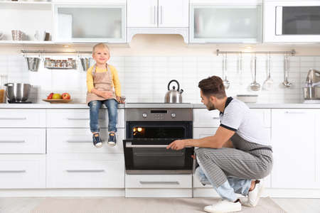 Young man and his son baking something in oven at home 版權商用圖片 - 112948750