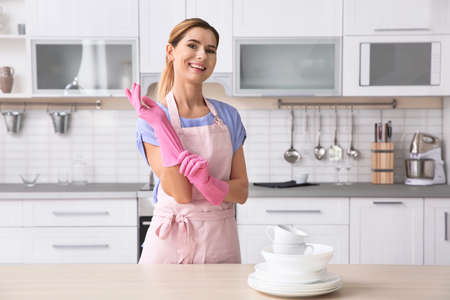 Woman wearing rubber gloves near table with clean dishes and cups in kitchen