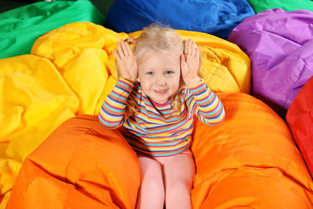 Cute child playing on colorful bean bag chairs indoors