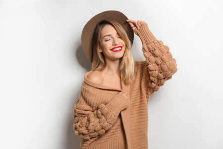 Beautiful young woman in warm sweater with hat on white background