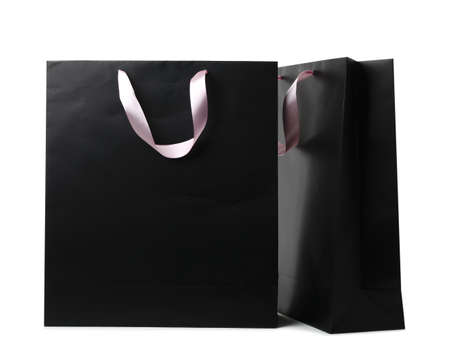 Paper shopping bags with ribbon handles on white background. Mockup for design