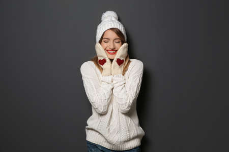 Beautiful young woman in warm sweater with hat and mittens on dark background