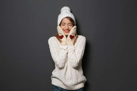 Hermosa joven en suéter caliente con sombrero y guantes sobre fondo oscuro Foto de archivo