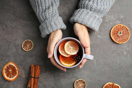 Woman in warm sweater with cup of hot winter drink on gray background, top view. Cozy season