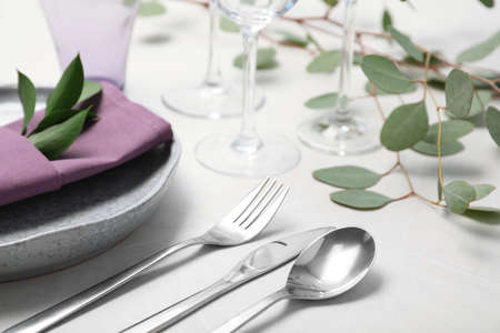 Cutlery, plate and napkin on light background, closeup. Festive table setting
