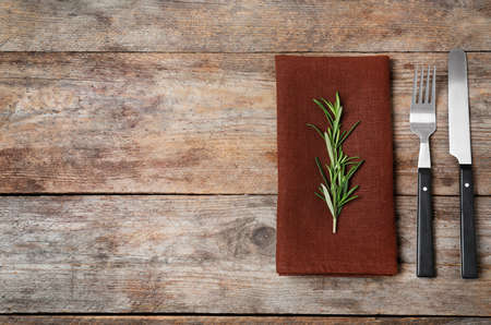 Fork, knife and napkin on wooden background, flat lay. Space for text