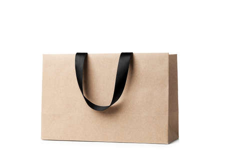 Paper shopping bag with ribbon handles on white background. Mockup for design