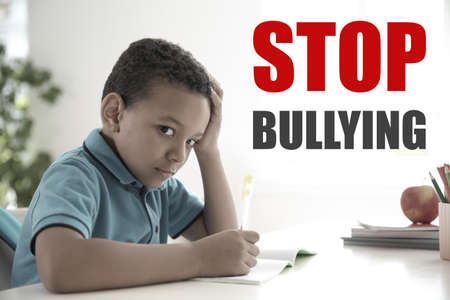 Sad little African-American boy sitting at desk in classroom and message STOP BULLYING on background