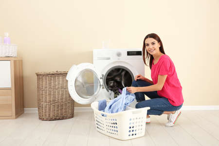 Young woman taking laundry out of washing machine at home Foto de archivo