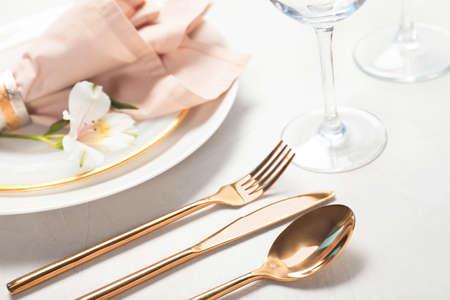 Złote sztućce i talerze z serwetką na jasnym tle, zbliżenie. Świąteczne nakrycie stołu