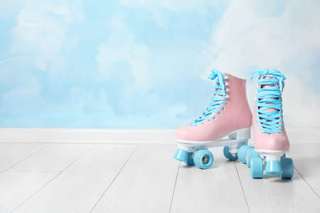 Vintage roller skates on floor near color wall. Space for text