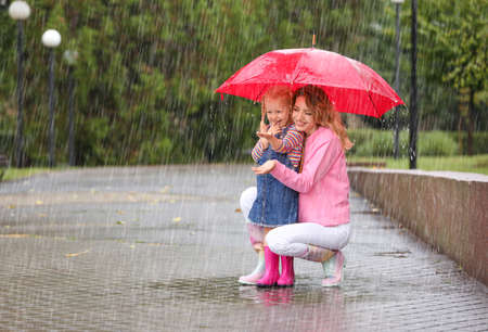 Happy mother and daughter with red umbrella in park on rainy day. Space for text Stockfoto