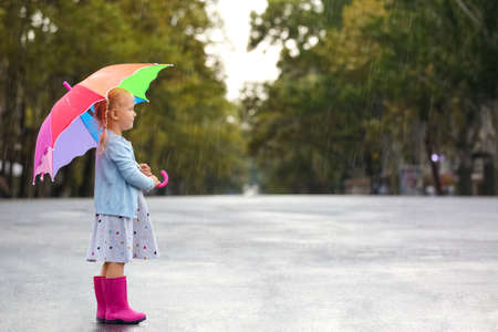 Cute little girl with umbrella in city on rainy day. Space for text