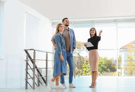 Agente inmobiliario femenino que muestra la nueva casa a la pareja, en el interior