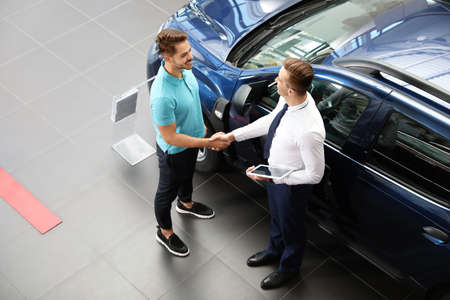 Young car salesman shaking hands with client in dealership