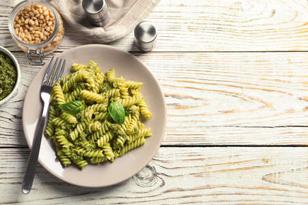 Flat lay composition with plate of delicious basil pesto pasta and space for text on wooden table