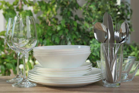 Clean dishes, shiny cutlery and glasses on wooden table against blurred background