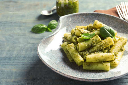 Plate with delicious basil pesto pasta on wooden table