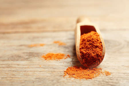Scoop with powdered red pepper on wooden table. Space for text