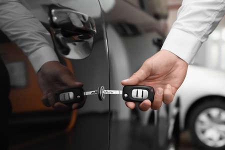 Young man opening car with key indoors, closeup Stock Photo