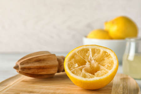 Wooden board with lemon reamer and squeezed fruit on table