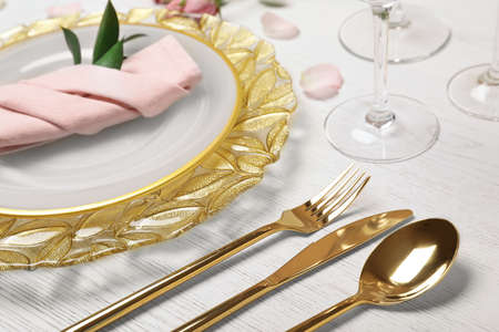Festive table setting with plates, cutlery and napkin on wooden background, closeup