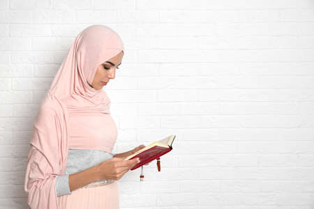 Young Muslim woman in hijab reading Koran against brick wall. Space for text 免版税图像