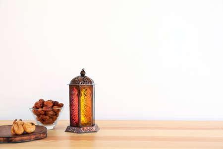 Muslimische Laterne Fanous und Trockenfrüchte auf dem Tisch vor hellem Hintergrund. Platz für Text