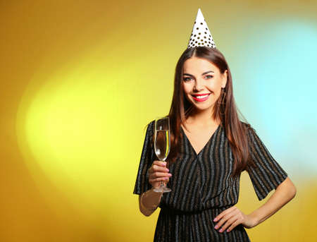 Portrait of happy woman with party hat and champagne in glass on color background