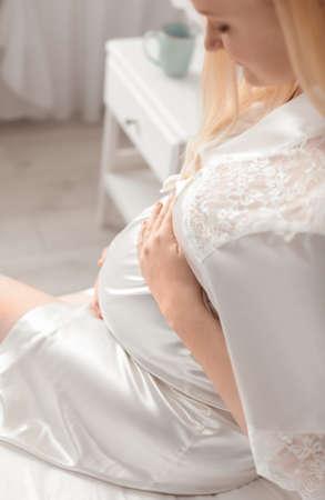 Pregnant woman in bathrobe sitting at home Standard-Bild - 134482215