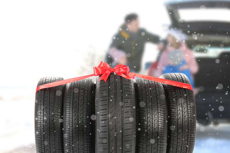 Gift set of winter tires and happy family on background. Car store service