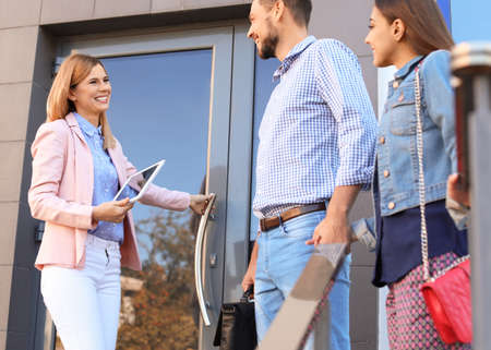 Female real estate agent welcoming couple to show house, outdoors Stock Photo