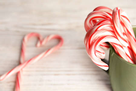 Tasty candy canes in cup on wooden table. Space for text
