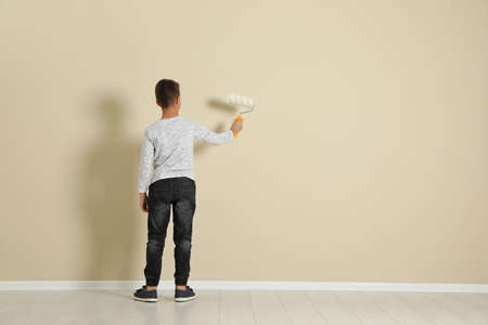 Child painting color wall with roller brush. Space for text Banque d'images - 112490903