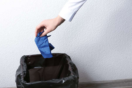 Woman throwing out paper napkin into rubbish bin, closeup Stockfoto