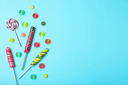 Flat lay composition with different candies and space for text on color background