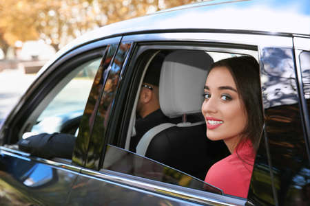 Young businesswoman with driver in car. Chauffeur service