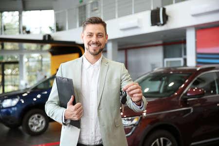 Sprzedawca ze schowkiem i kluczykami do samochodu w nowoczesnym salonie samochodowym
