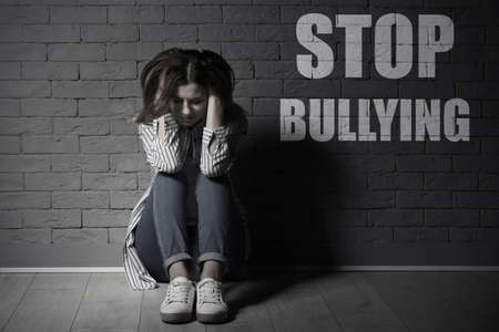 Message STOP BULLYING and sad woman sitting on floor near brick wall, black-white effect