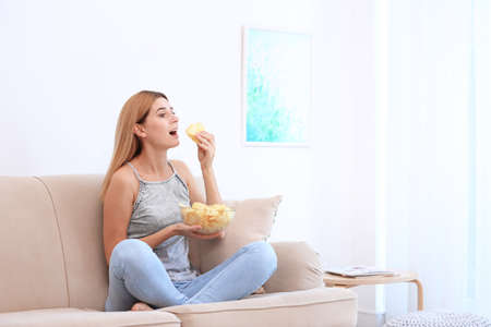 Woman with bowl of potato chips sitting on sofa in living room. Space for text