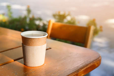 Cardboard coffee cup on wooden table outdoors. Space for text